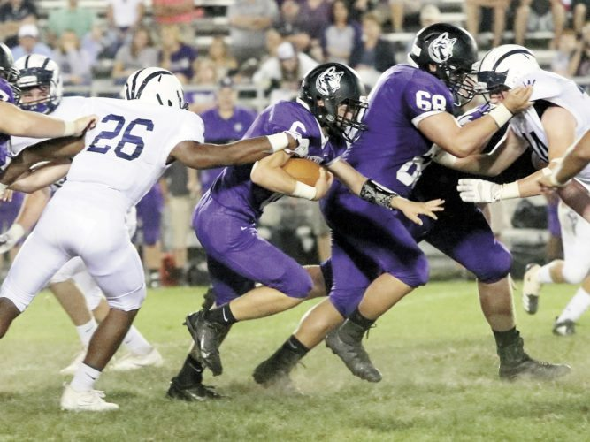 Sentinel photo by MATT STRICKER Mifflin County's Gage Scheaffer (6) follows blocker Caleb Yoder (69) while being pursued by Wyomissing's Alyas Branford-Williams (26) Friday in Lewistown.