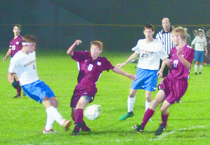 Sentinel photo by TIM SHUMAKER  Greenwood's Bo Gothel (4) kicks the ball away from East Juniata's Cade Brubaker (6) as Glenn Rice (27) and Adam Finkbiner (17) join the play Thursday evening in Millerstown.