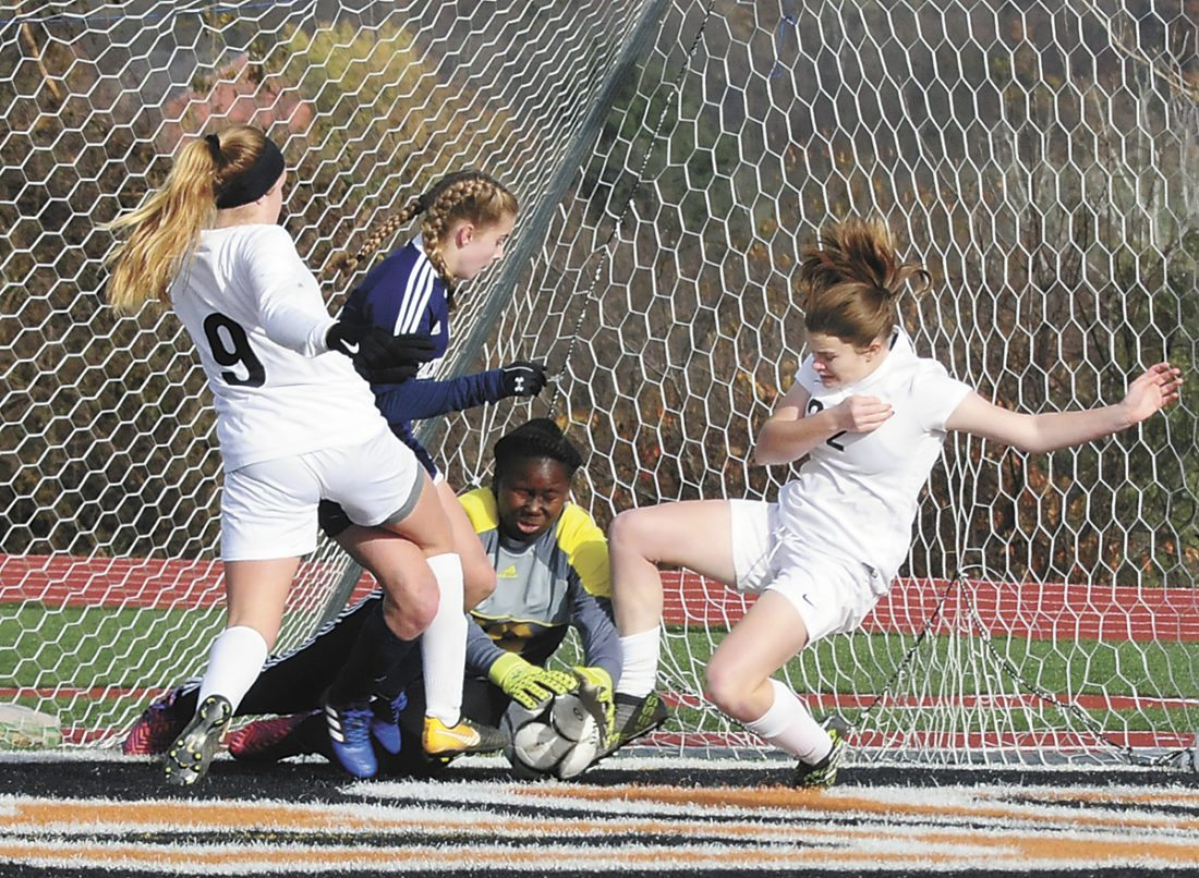 Sentinel photo by TIM SHUMAKER Calvary Christian goalie Celeste Sanchez blocks an attempt by East Juniata's Thea Neimond (9) and Brianna Henry (22) as Calvary Christian's Allison Stuart assists Saturday during a PIAA Class A girls soccer quarterfinal game in Manchester.
