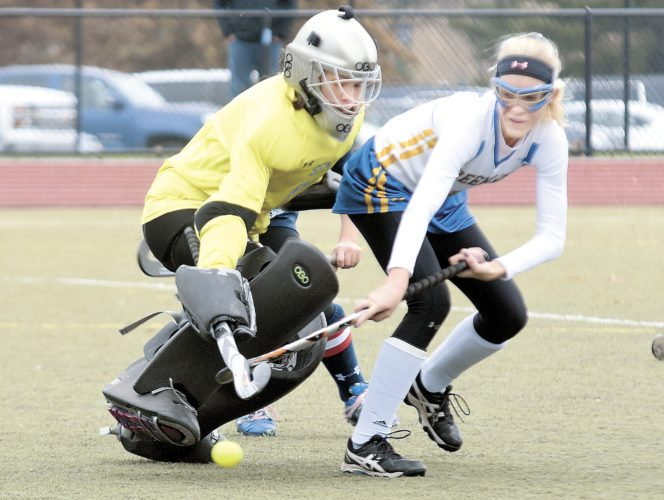 Sentinel photo by BUFFIE BOYER  Greenwood's Leah Bryner, right, slips the ball past Wyoming Seminary goalie Mia Magnotta in the final minute of the first half Saturday in Whitehall. Th goal stood as the game winner as Greenwood won the PIAA Class A field hockey championship, the school's first state title.