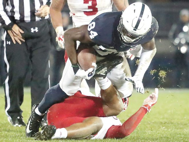 Sentinel photo by CHRISTOPHER SHANNON  Penn State's Juwan Johnson is tripped up by a Nebraska defender during the Nittany Lions' 56-44 win over the Cornhuskers Saturday.