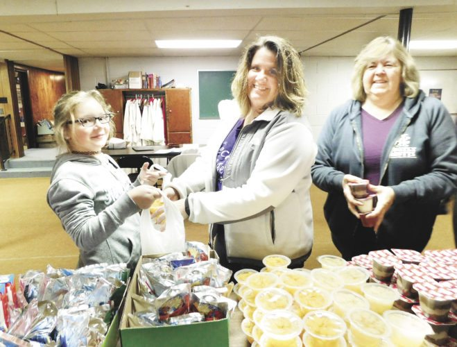 Submitted photo Volunteers, from left, Marley Wilson, Renee Snyder, and Terry Gross help pack Tiger Treat bags to provide meals for children in need.
