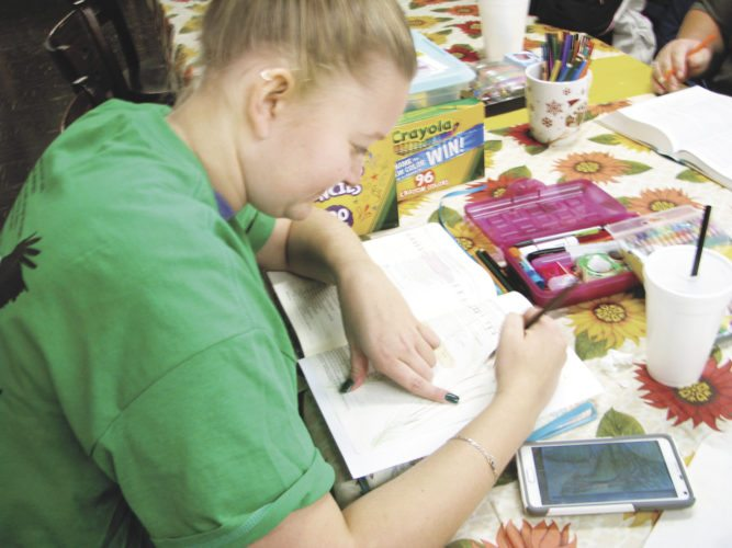 Sentinel photo by TABITHA GOODLING Joelle Henry works on a page during a Bible Journaling workshop.