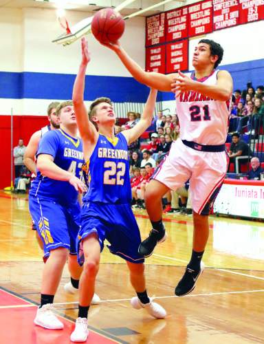 Sentinel photo by MATT STRICKER  Juniata's Jamie Bailer, right, attempts a layup over the outstretched arms of Greenwood's Aaron Bollinger Monday in Mifflintown.