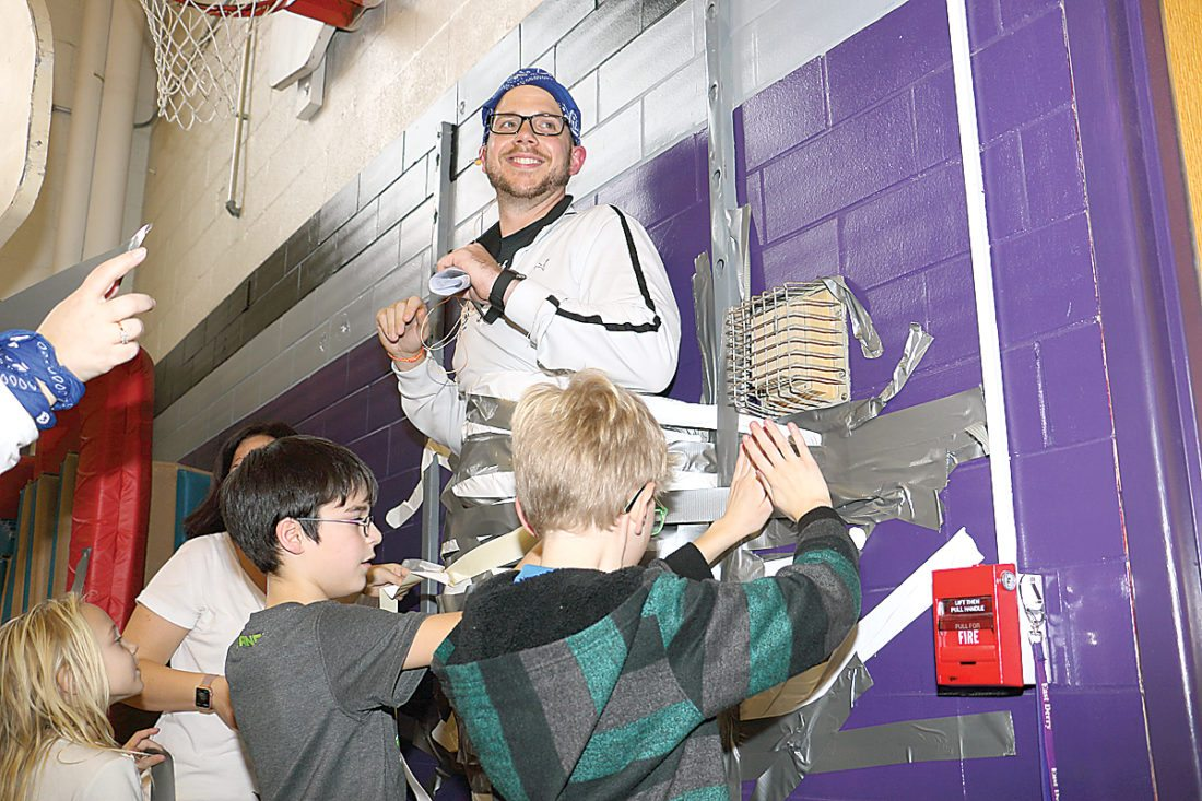 Sentinel photo by MATT STRICKER Indian Valley Elementary School Principal Kevin O'Donnell gets taped to the wall with help from fifth graders Conner Dippery, left, and third grader Hoyt Rodenbaugh during the positive behavior event held Friday at the school in Reedsville.