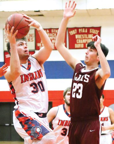 Sentinel photo by MATT STRICKER Juniata's Bryson Clark, left, attempts a lay up while defended by East Juniata's Bryce Martin Friday in Mifflintown.