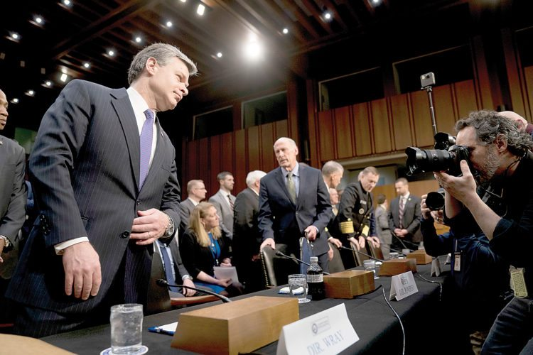 FBI Director Christopher Wray, left, and Director of National Intelligence Dan Coats, center, arrive for a Senate Select Committee on Intelligence hearing on worldwide threats, Tuesday, Feb. 13, 2018, in Washington. (AP Photo/Andrew Harnik)