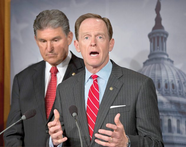 FILE - In this April 10, 2013, file photo, U.S. Sen. Patrick Toomey, R-Pa., right, speaks alongside U.S. Sen. Joe Manchin, D-W.Va., left, as they discuss reaching a bipartisan agreement that would expand background checks to more gun buyers, during a news conference on Capitol Hill in Washington. Toomey said Wednesday, Feb. 21, 2018, that he'll probably reintroduce legislation to expand background checks on gun purchases, but that the proposal may require changes compared to previous efforts that failed at least twice. The bill never exceeded 54 votes, short of the 60 necessary. (AP Photo/J. Scott Applewhite, File)