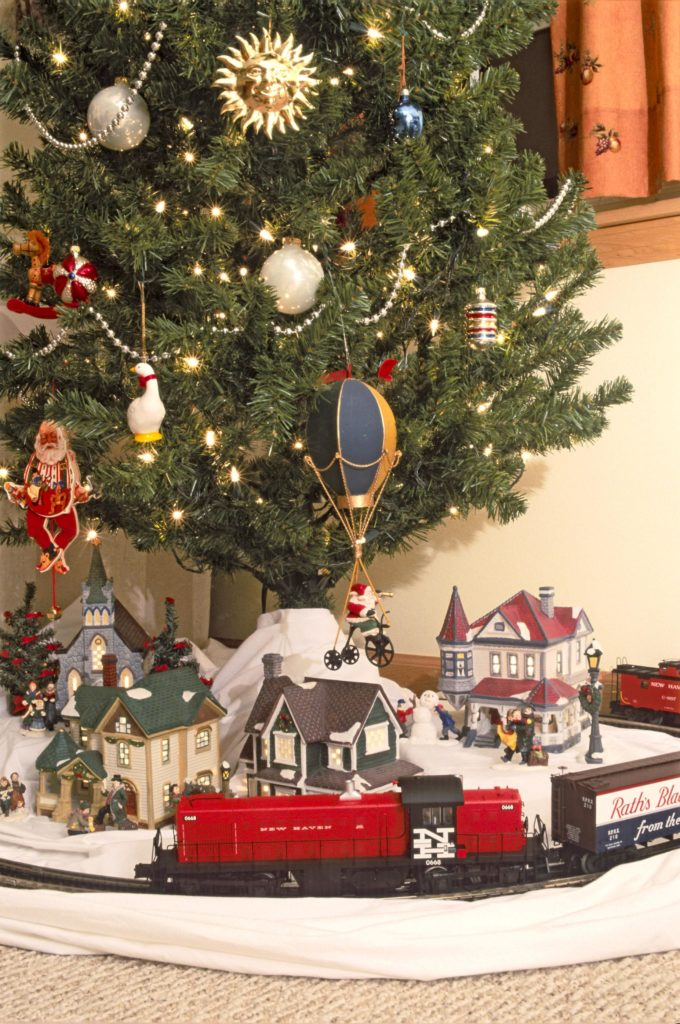 model railroader magazine shows a model train under a christmas tree memories are what often bring out christmas tree trains this time of the year