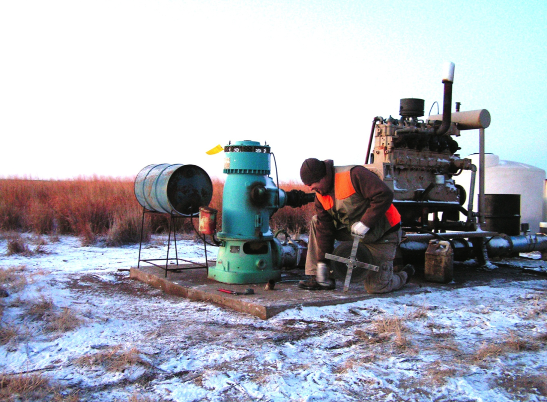 Brett Wedel, a field research assistant, with the Kansas Geological Survey, checks a well east of Liberal on a previous January trip to measure groundwater levels.