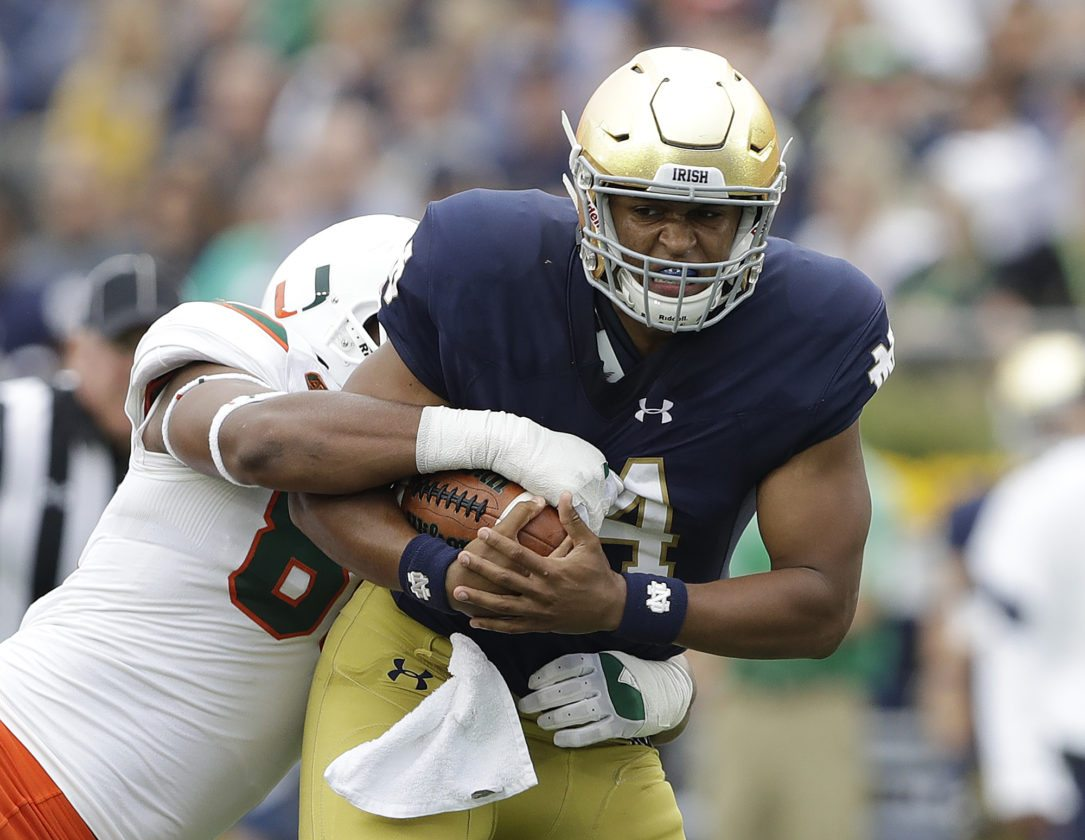 Notre Dame quarterback DeShone Kizer (14) is tackled by Miami 's RJ McIntosh during the first half of an NCAA college football game Saturday, Oct. 29, 2016, in South Bend, Ind. (AP Photo/Darron Cummings)