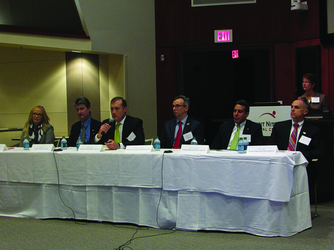 EMMAGOSALVEZ/THEEXPRESS Daryl Bloom, third from left, Assistant United States Attorney for the Middle District of Pennsylvania, discussed what his office has been doing to fight the opioid and heroin epidemic, which has included working with local officials and the state Legislature and targeting major drug traffickers. Also on the panel were, from left: Centre County District Attorney Stacy Parks-Miller, Scott Sayers of the Centre County coroner's office, Patrick Trainor of the Drug Enforcement Administration, Juan Grajales of the FBI, and Sean Noel of the FBI. The woman behind the podium is Ferguson Township Police Chief Diane Conrad.