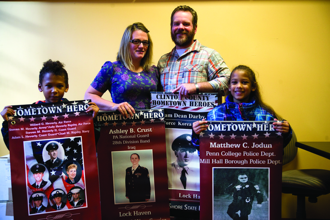 At right, Kevin and Kristy Eichenlaub hold Hometown Hero Banners, standing behind Najiah Staton, left, and Nasier Staton, also holding banners. The Eichenlaubs were among the first to purchase a Hometown Hero banner. Kevin served in the U.S. Army Reserves for 15 years and spent one tour in Iraq. He and his wife operate Kraft & Karry, 228 E. Main St. downtown. The Statons were walking by the Downtown Lock Haven Inc. office at 205 E. Main St. — banner central — and agreed to help promote the Hometown Hero Program by displaying past banners with the Eichenlaubs.
