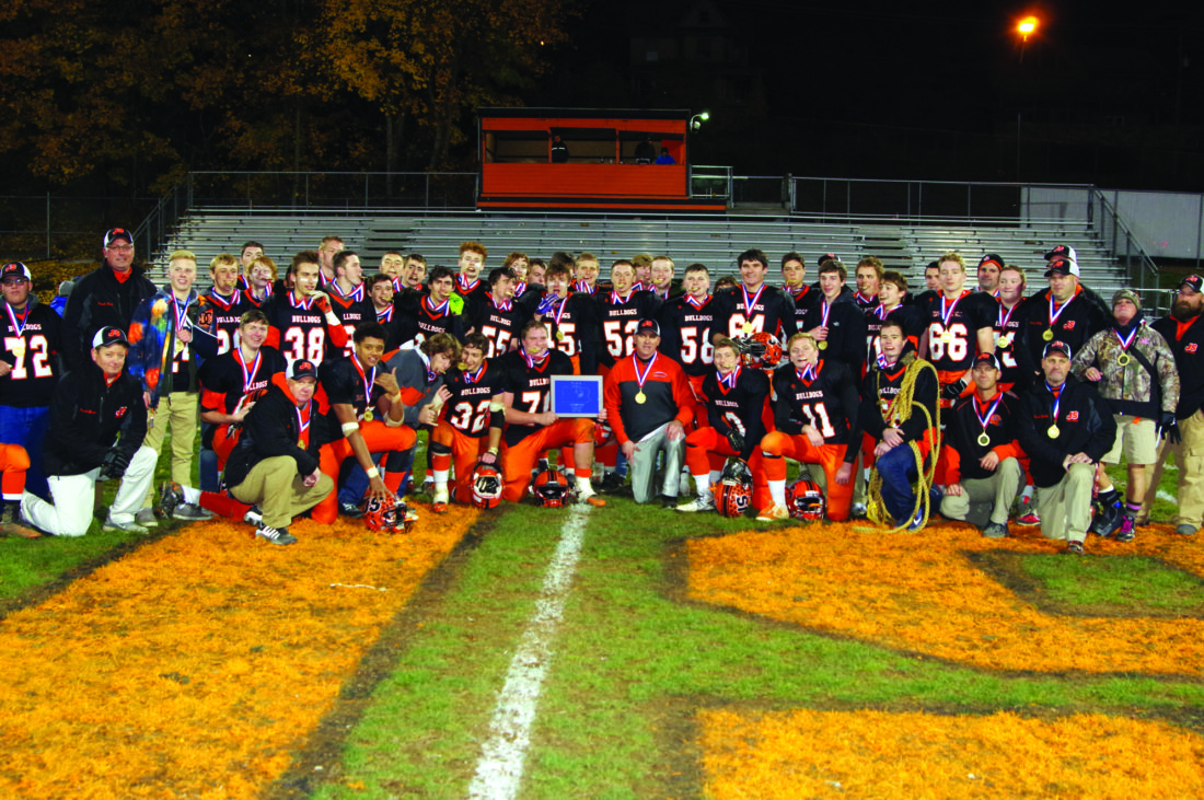 Head Coach Tom Gravish (center bottom right) and his Jersey Shore High School Bulldogs celebrate winning the PIAA AAAA District 4 Championship. They defeated Selinsgrove 31-15 in the championship game.