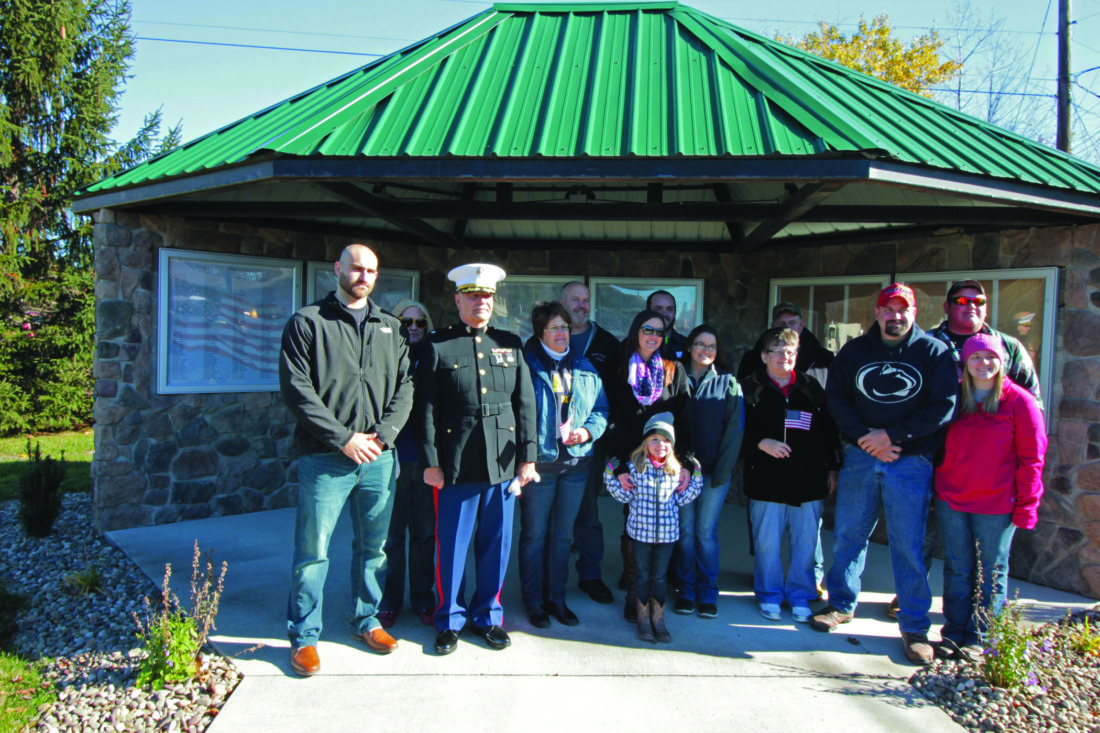 PHOTO PROVIDED Attendees pose in front of the memorial wall at Avis Veterans Memorial Park Saturday, when a ceremony was held to dedicate the park.