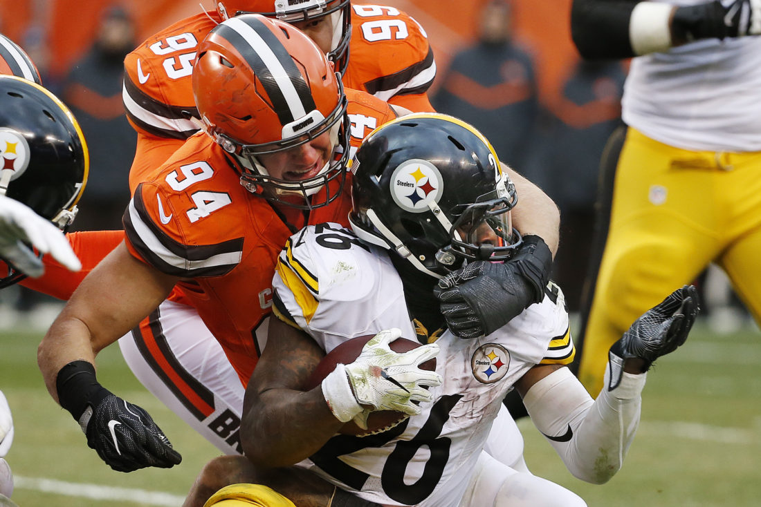Pittsburgh Steelers running back Le'Veon Bell (26) is tackled by Cleveland Browns defensive end Carl Nassib (94) during the second half of an NFL football game in Cleveland, Sunday, Nov. 20, 2016. (AP Photo/Ron Schwane)