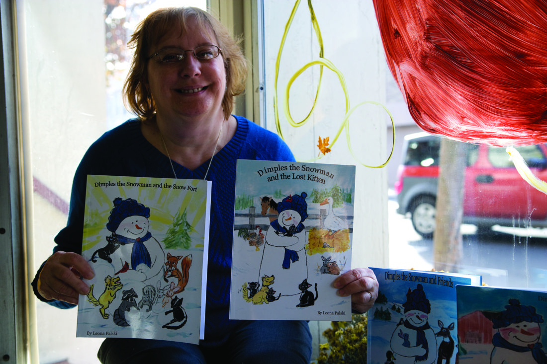 "SPENCER McCOY/THE EXPRESS Author, painter and photographer Leona Palski displays her four ""Dimples the Snowman"" books. Her latest book — ""Dimples the Snowman and the Snow Fort"" — is now available ... call her at 570-772-9680 and she'll see that you get a signed copy in time for Christmas giving."