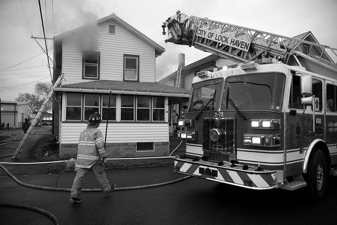 SPENCER McCOY/THE EXPRESS Firefighters work at the scene of a blaze on Commerce Street in Lock Haven yesterday.