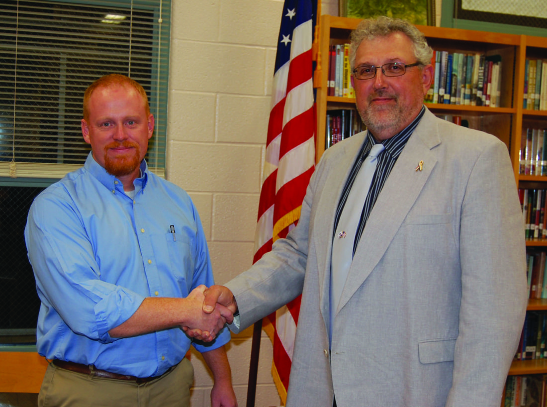 JIM RUNKLE/THE EXPRESS Keystone Central School Board President James Knauff, right, shakes hands with chief negotiator for the Association of Clinton County Educators Tom Temple, after the two sides agreed to a four-year contract Thursday. The ACCE, representing approximately 360 teachers, ratified the contract yesterday.