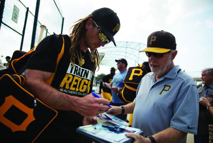 Pittsburgh Pirates' John Jaso, left, signs autographs for fans at baseball spring training in Bradenton, Fla., Tuesday, Feb. 14, 2017. (AP Photo/David Goldman)