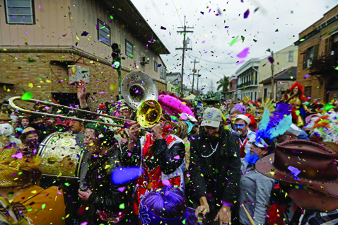FILE - In this Feb. 17, 2015, file photo, revelers play brass band music as they begin the march of the Society of Saint Anne Mardi Gras parade, during Mardi Gras in New Orleans. The NBA All-Star Weekend gets underway in New Orleans on Friday, Feb. 17: the same day the city's Mardi Gras season kicks into high gear. Floats, marching bands and street parties will compete with, or maybe complement, slam dunks, three-point plays and buzzer beaters. (AP Photo/Gerald Herbert, File)