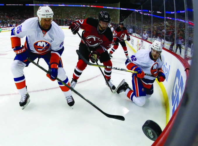New Jersey Devils center Pavel Zacha, center, of the Czech Republic, competes for the puck with New York Islanders left wing Jason Chimera (25) and defenseman Scott Mayfield (42) during the first period of an NHL hockey game, Saturday, Feb. 18, 2017, in Newark, N.J. (AP Photo/Julio Cortez)