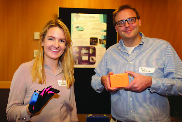 PHOTO BY ALS Association and Prize4Life Mary Elizabeth McCulloch, founder and CEO of Project Vive, and Trip Miller, CFO, demonstrate how their product, the Voz Box, works. The Voz Box uses small movements from the knee, wrist or finger of the user to construct full sentences.
