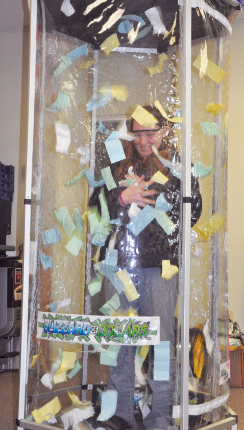 "KEVIN RAUCH/THE EXPRESS Pa. Lottery sets up fun booth in Renovo  Pennsylvania Lottery officials visited Puff-N-Snuff on Erie Avenue in Renovo and brought their wind tunnel booth with them, giving local lottery enthusiasts the chance to get a coupon for the newest game, ""Fast Play."" More than a hundred people stopped in Friday afternoon to take a chance on getting free vouchers to play the new instant ticket game. Officials on hand said the Renovo store received the promotion thanks to the Puff-N-Snuff's ticket sales and interest in the Pennsylvania Lottery. Jim Coover is in the wind tunnel grabbing for lucky pieces of green paper that could be exchanged for free Fast Play coupons."