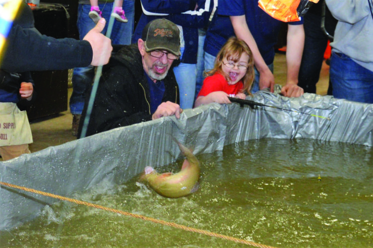 Grandpop Jeff Henzler and his granddaughter Rylee Frantz react to a large rainbow trout caught at the event.