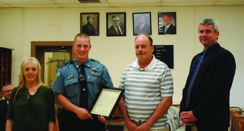 WENDY STIVER/THE EXPRESS Lock Haven Patrolman Adam Raybuck was commended during City Council's Monday evening meeting. With him are Morris L. Barrett, second from left, whose life he saved; Barrett's wife, Debra; and Police Chief Keith Kibler.