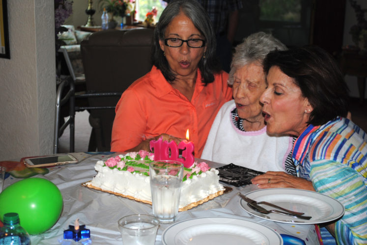 WENDY STIVER/THE EXPRESS Nancy Gregory blows out her candles with help from nieces Thalia Johanssen, left, and Mary Anne Scott.