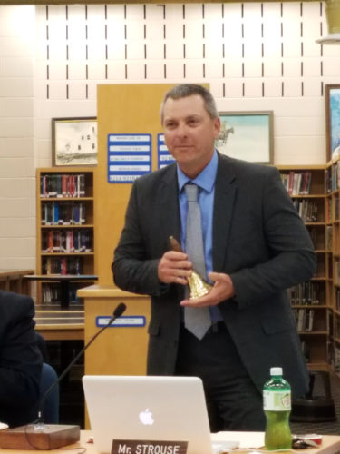 KEVIN MCKEE/The Express Greg Strouse holds a bell given to him by Keystone Central School District Superintendent Kelly Hastings at last night's school board meeting as a thank you for his years of service on the board. Strouse, a local attorney, has resigned due to professional and family commitments. The board membership could see significant change in the coming months up through the November election.