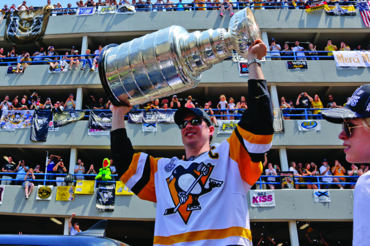 Pittsburgh Penguins' Sidney Crosby hoists the Stanley Cup while riding in the Stanley Cup victory parade in Pittsburgh, Wednesday, June 14, 2017. (AP Photo/Gene J. Puskar)