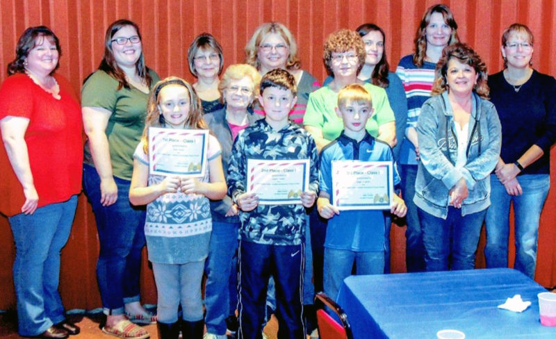 In front are the third and fourth grades winners, from left: Cora Myers in first place, Jacob Clymer  in second place, and Gage Laughner in third place. Auxiliary members are, from left: President Billie Orndorf, sergeant at arms Marsha Windle, treasurer Linda Bechdel, assistant treasurer Sandy Gensib, secretary Harriet Edwards, Ruth Hunter, second sergeant at arms Clara Windle, chaplain Bobbie Miller, Debbie Lesser and Jodi Koch.
