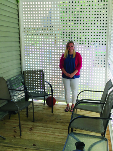 Jacqueline Armstrong, new youth advocate at the Clinton County Women's Center, is seen on the newly repaired back porch at the facility.