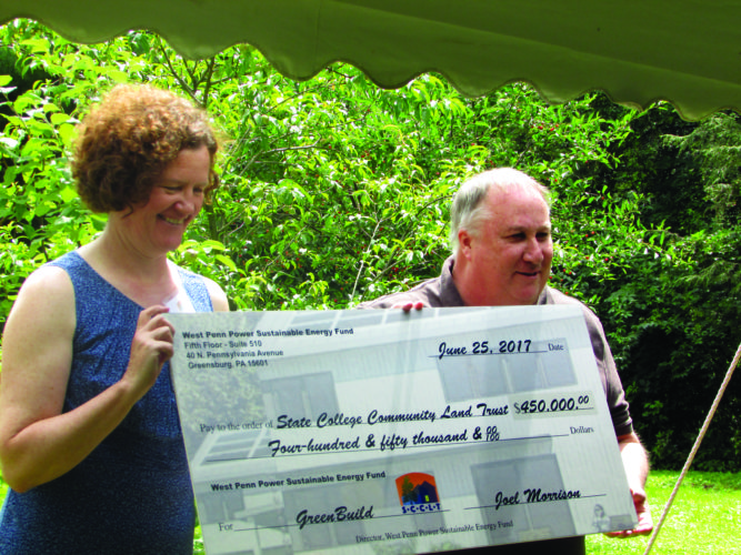 EMMA GOSALVEZ/THE EXPRESS Joel Morrison of the West Penn Power Sustainable Energy Fund (WPPSEF) presents a $450,000 check to Colleen Ritter, executive director of the State College Community Land Trust (SCCLT). In early June, WPPSEF awarded SCCLT with a $100,000 grant and a $350,000 construction loan to help fund the construction of GreenBuild.