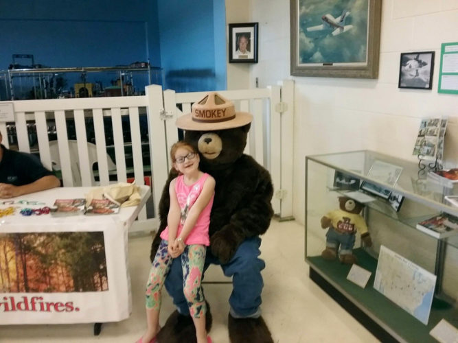 PHOTO PROVIDED Elizabeth Litz, 8, of Lock Haven sits on Smokey Bear's lap Saturday at the Piper Aviation Museum in Lock Haven.