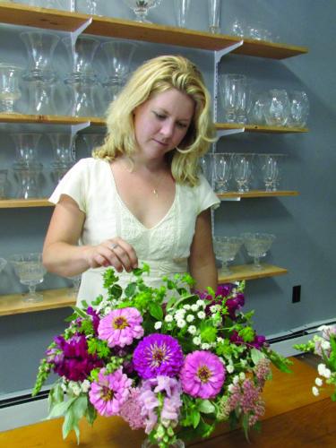EMMA GOSALVEZ/THE EXPRESS Erin Carey arranges a flower bouquet in her boutique.