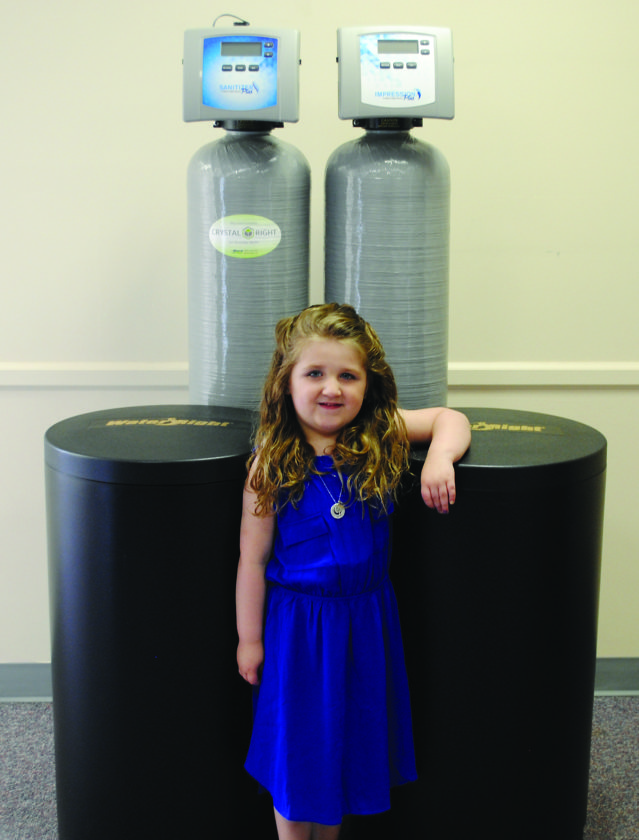 JORDAN SLOBODINSKY/THE EXPRESS Sylvia Benner stands in front of a water treatment system at her father's new business, Wisdom Water Treatment, in Dunnstown.