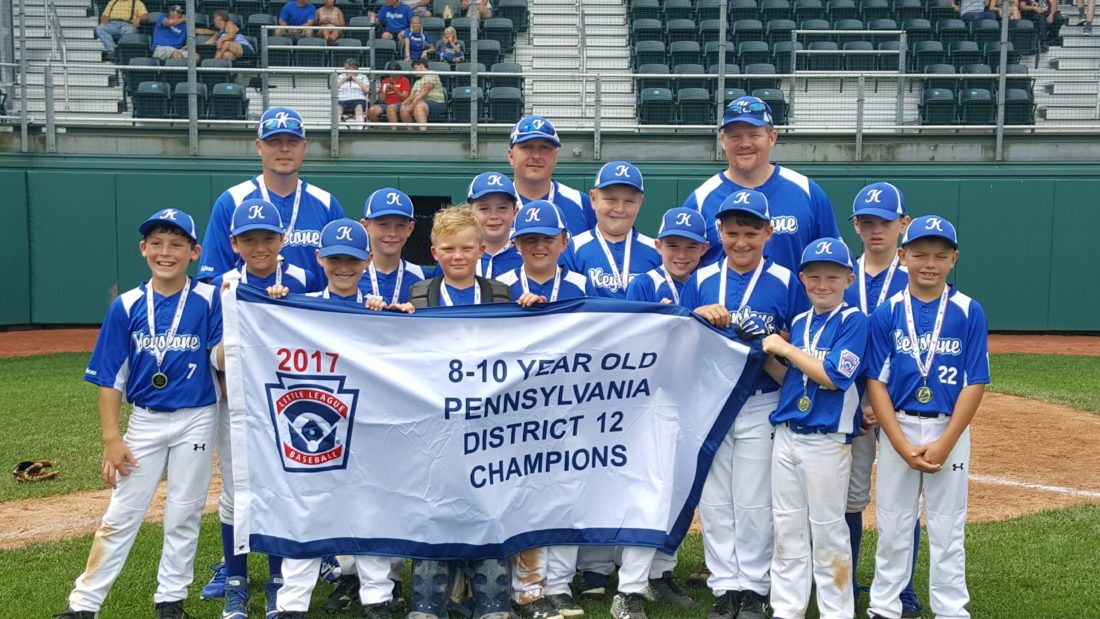 The Keystone 8-10 All-Stars celebrate with their District 12 Championship banner after winning the title game against the Loyalsock 8-10 All-Stars, 6-2, on Saturday. Keystone moves on to the sectional tournament starting this week. (The Express/Shareik Flowers)