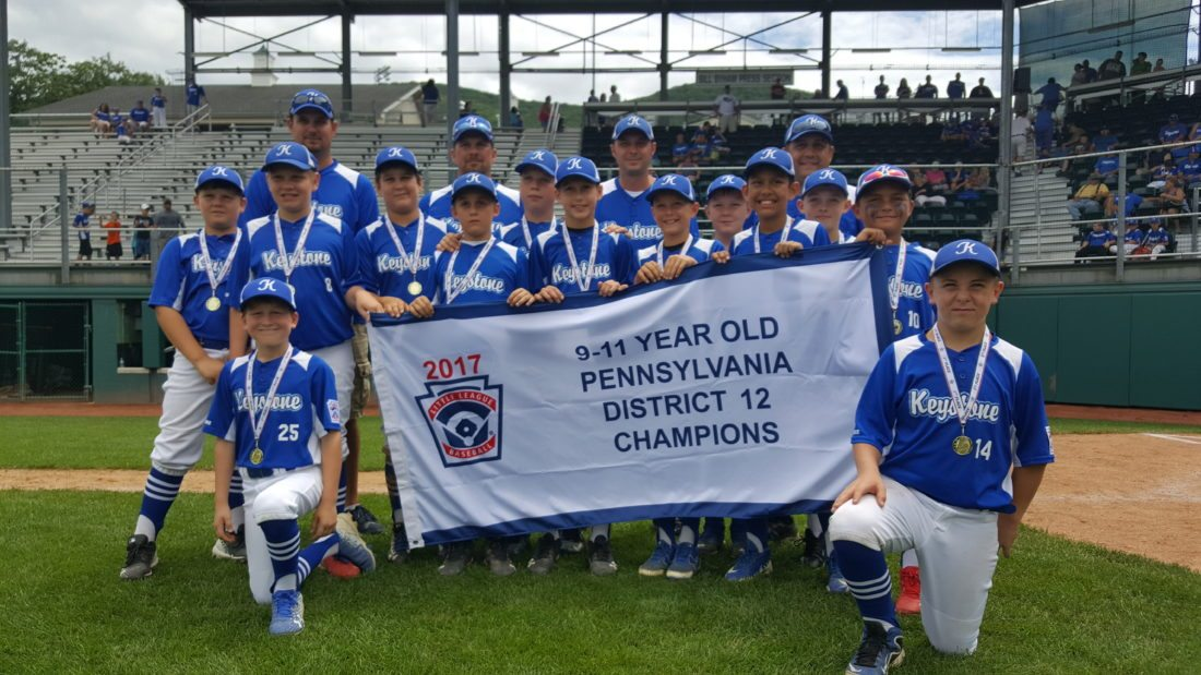The Keystone 9-11 All-Stars pose with their District 12 Championship banner on Saturday after beating Montoursville, 11-1. (The Express/Shareik Flowers)