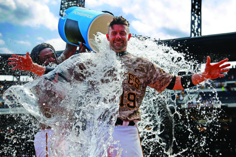 Pittsburgh Pirates' Chris Stewart, center, gets doused by Josh Bell as he waits to be interviewed after a 4-2 Pirates win over the Milwaukee Brewers in a baseball game in Pittsburgh, Thursday, July 20, 2017. (AP Photo/Gene J. Puskar)