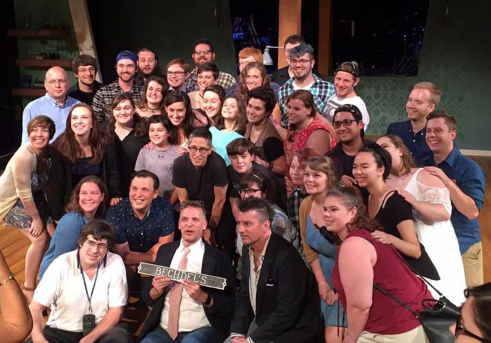 """The cast and other Millbrook company members pose with the Bechdels. At front center is Artistic Director David Leidholdt, holding the """"Bechdel's"""" sign. Alison is directly behind him, Christian is on his right (our left), in front, and John is on his left. Also in the photo are people from our region, including actors Dane Hanna, Kali Haines and Joey Watkins, artistic associate and director of theatre education Matt Spencer, far right, and general business manager David Gritzner, far left."""