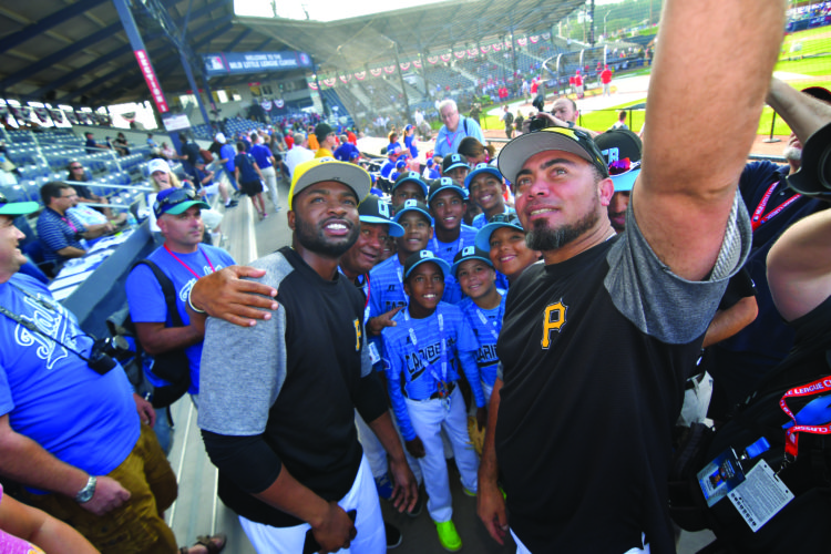 MARK NANCE/Sun-Gazette Members of the Pittsburgh Pirates pose for a selfie with members of the Caribbean team before the Little League Classic at Bowman Field Sunday.