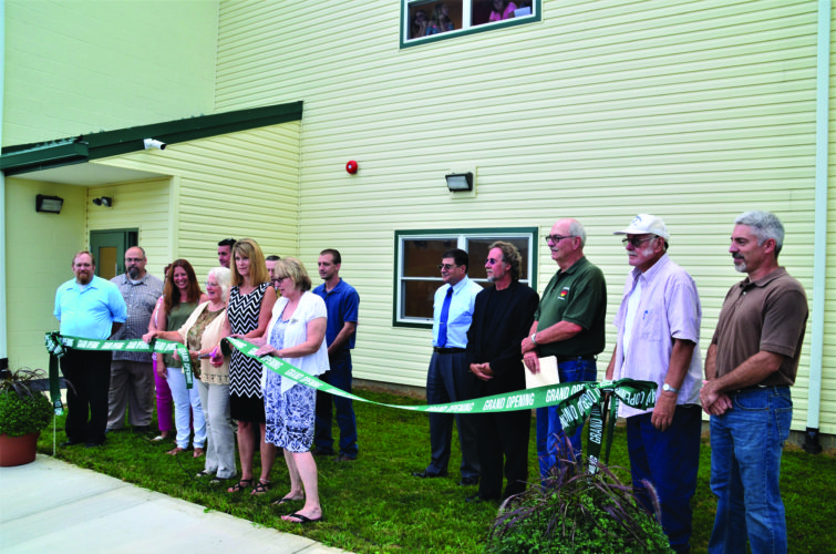 AMBER MORRIS/FOR THE EXPRESS Sugar Valley Rural Charter School officials cut the ribbon on the new building during a ceremony held Monday night.