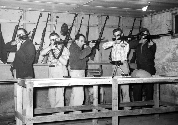 "EXPRESS ARCHIVES This photo of the Mill Hall Fire Company Rifle Team, possibly taken in the late 1950s, was published in The Express ""Old Photo Album"" on Wednesday, and that very morning, team member Ted Reeder called to identify most of his teammates. Mike Ryan also called to fill in some information, and we thank them both. Between them, they think the shooters are, from left, a shooter who may or may not be Ted Hills, then Mike Ryan, Jack Streck, Ed Ryan, and Ted Reeder. This photo was taken during a match in the basement of Albright's Barber Shop, across from the old Mill Hall Fire Station on Pennsylvania Avenue, no later than 1959."