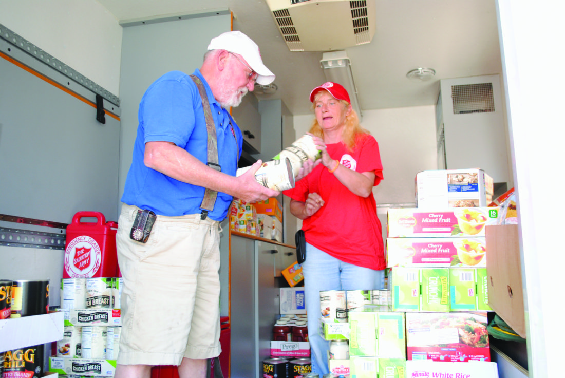 WENDY STIVER/THE EXPRESS Jim Gill and Nancy Brown, seen here loading a truck with supplies, are headed to a hurricane-lashed area in Florida with the mobile canteen from the Salvation Army in Lock Haven.