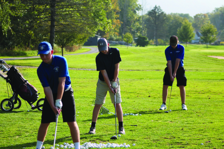 Front to back: Central Mountain golfers and PHACChampions Logan Fisher, Chase Confer and Bryon Carey practice their tee shots. (The Express/Scott Baker)