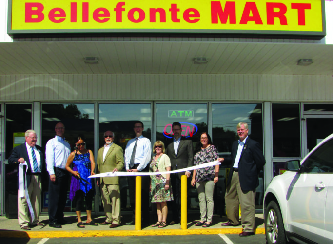 At noon on Friday, Bellefonte Mart had its grand opening. From left to right: Gary Hoover, BIACC executive director; Commissioner Mark Higgins; owner Dolly Singh; Bellefonte Mayor Tom Wilson; Commissioner Mike Pipe; Renee Brown of the Central PA Convention and Visitors Bureau; Bellefonte Borough Manager Ralph Stewart; Lori Miller, interim executive director of the Central PA Convention and Visitors Bureau; and Assistant Borough Manager Don Holderman.  EMMA GOSALVEZ/ THE EXPRESS
