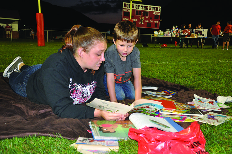 "Caitlyn Conti reads to her son Jace White on Dwyer Memorial Field during ""Reading Under the Lights,"" a KeystoneCares Initiative that encourages reading while allowing students a unique experience of sitting on the Bucktail Area High School football field. Family members, friends and in this case neighbors, all take part in Reading Under the Lights.  KEVIN RAUCH/THE EXPRESS"